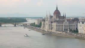 Paesaggio urbano di stupore a Budapest, costruzione ungherese del Parlamento, traffico di automobile sull'argine di Danubio stock footage