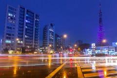 Paesaggio urbano di Tokyo con i semafori e la torre illuminata di Tokyo, Giappone Immagine Stock