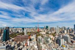 Paesaggio urbano di Tokyo di costruzione e del fondo rosso del cielo blu della torre Immagini Stock