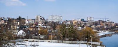 Paesaggio urbano in molla in anticipo Alberi nudi colpiti dal vischio, dalle costruzioni, dal fiume e dal cielo blu Immagini Stock Libere da Diritti