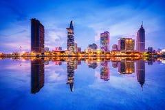 Paesaggio urbano nella riflessione della città di Ho Chi Minh a bella penombra, osservata sopra il fiume di Saigon fotografia stock
