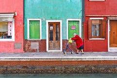 Paesaggio urbano pittoresco con le passeggiate anziane della donna con un istitutore del carretto lungo il canale dell'acqua nell fotografie stock libere da diritti