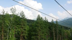 Paesaggio variopinto della montagna di estate luminosa con il cielo nuvoloso e l'ascensore di sci blu Vista dalla montagna di alz stock footage