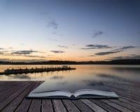 Paesaggio vibrante di alba del molo sul libro concettuale del lago calmo Fotografie Stock Libere da Diritti