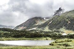 Paesaggio vulcanico con le pianure verdi e lago sulla penisola di Kamchatka, Russia immagini stock libere da diritti