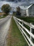 Paese dell'Ohio Amish con un granaio e un recinto bianco immagine stock