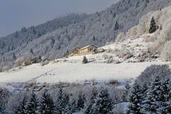 Paesino di montagna a distanza con le cime delle montagne innevate Immagini Stock Libere da Diritti
