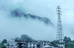 Paesino di montagna e torre ad alta pressione Fotografie Stock