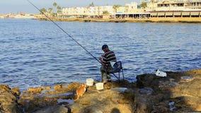 Pafo, Cipro - 17 settembre 2017 - pescatore con la canna da pesca alla riva stock footage