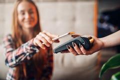 Paga de la mujer joven por el teléfono móvil en café fotografía de archivo