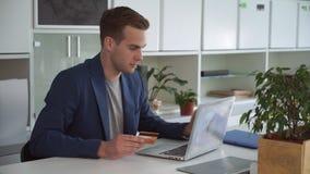 Paga dell'uomo d'affari online dalla carta di credito nell'ufficio moderno video d archivio