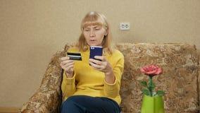 Paga mayor de la mujer para las compras en la tarjeta de crédito bancaria de Internet Ella introduce cuidadosamente un número de  metrajes