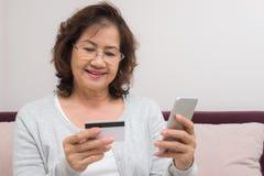 Paga online di compera della donna senior asiatica felice con la carta di credito Fotografia Stock