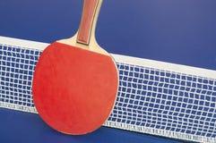 Pagaia e rete di ping-pong su una tavola Immagini Stock Libere da Diritti