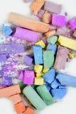 Pagaille de couleurs cassée par craie colorée au-dessus de blanc Photographie stock