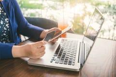 Pagamenti mobili Mani femminili facendo uso dello smartphone e della carta di credito f fotografia stock