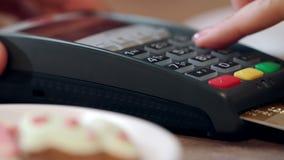 Pagamento con carta di credito in caffè La mano della donna imposta il codice del perno sul terminale di pagamento stock footage