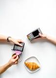 Pagamento con carta di credito in caffè sul modello bianco di vista superiore del fondo della tavola Fotografia Stock