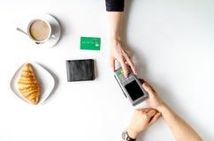 Pagamento con carta di credito in caffè sulla vista superiore del fondo bianco della tavola Immagini Stock