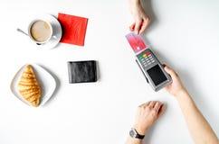 Pagamento con carta di credito in caffè sulla vista superiore del fondo bianco della tavola Immagine Stock