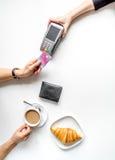Pagamento con carta di credito in caffè sulla vista superiore del fondo bianco della tavola Immagine Stock Libera da Diritti