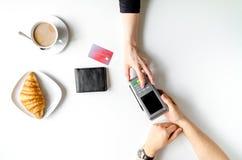Pagamento con carta di credito in caffè sulla vista superiore del fondo bianco della tavola Fotografia Stock