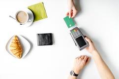 Pagamento con carta di credito in caffè sulla vista superiore del fondo bianco della tavola Fotografia Stock Libera da Diritti