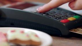 Pagamento con carta di credito per ordine in caffè La mano della donna imposta il codice del perno archivi video