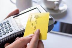 Pagamento in concetto del caffè con la carta e terminale su fondo bianco Fotografie Stock