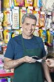 Pagamento de sorriso de Accepting Credit Card do vendedor do cliente imagens de stock royalty free
