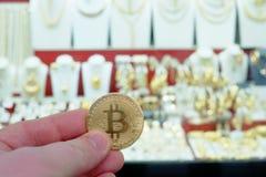 Pagamento di Bitcoin per gioielli ad un negozio facendo uso del concetto di cryptocurrency in realtà Fotografia Stock Libera da Diritti