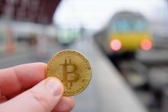 Pagamento di Bitcoin per il viaggio ad una stazione ferroviaria facendo uso del cryptocurrency Immagini Stock