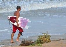 Pagamento do surfista para enganar com o mar foto de stock