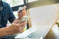 Pagamento em linha, as mãos do homem que guardam o telefone esperto Fotos de Stock Royalty Free