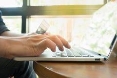 Pagamento em linha, as mãos do homem que guardam um cartão de crédito Fotos de Stock