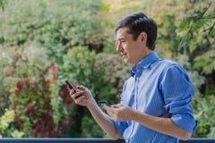 Pagamento online Equipaggi la tenuta della carta di credito e per mezzo dello Smart Phone per l'acquisto di Internet Vendita nel  fotografia stock libera da diritti