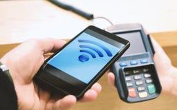 Pagamento pelo smartphone através do terminal Homem com pagamento móvel do smartphone na loja imagens de stock royalty free