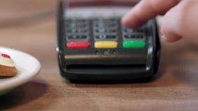 Pagamento terminale di posizione in caffè La mano della donna imposta il codice del perno sul terminale di pagamento video d archivio