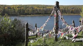 Pagan colorful cloth for spirits on the cliff over river. Religious video stock video footage