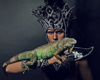 Pagan priest in ritual suit with green iguana Royalty Free Stock Images