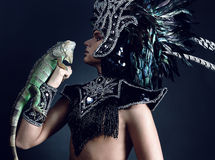 Pagan priest in ritual suit with green iguana Stock Images