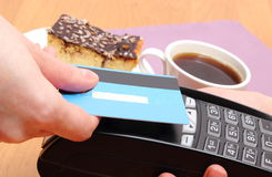 Pagando con la carta di credito senza contatto la torta di formaggio ed il caffè in caffè, concetto di finanza fotografie stock libere da diritti
