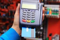 Pagando con la tarjeta de crédito en una tienda eléctrica, concepto de las finanzas Imágenes de archivo libres de regalías