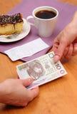 Pagando el pastel de queso y el café en el café, concepto de las finanzas Imagen de archivo libre de regalías