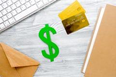 Pagando il concetto studing con il simbolo di dollaro e le carte sul modello leggero di vista superiore del fondo della tavola Fotografia Stock
