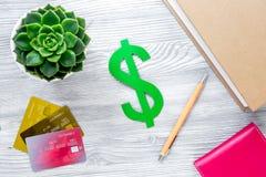 Pagando il concetto studing con il simbolo di dollaro e le carte sulla vista superiore del fondo leggero della tavola Fotografia Stock