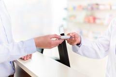 Pagando nella farmacia fotografia stock libera da diritti