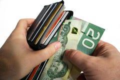 Pagando o dinheiro com moeda canadense imagem de stock royalty free