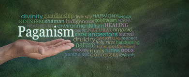 Paganism Word Cloud. Male hand outstretched on a green stone effect background with the word PAGANISM floating above surrounded by a relevant word cloud royalty free stock photo