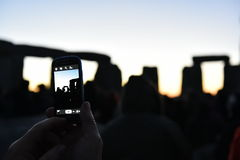 Pagans Mark the Autumn Equinox at Stonehenge. A reveller uses a smartphone to capture Stonehenge as pagans and druids celebrate the spring equinox at the ancient Stock Photography
